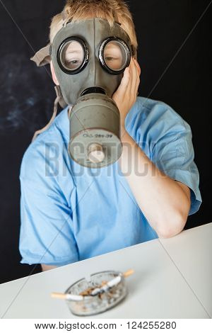Cigarettes in glass ash tray in front of sad blond child wearing chemical gas mask and blue shirt