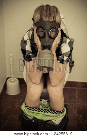 Child In Gas Mask Sitting On Toilet