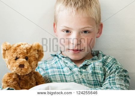 Cute Young Blond Boy With A Teddy Bear