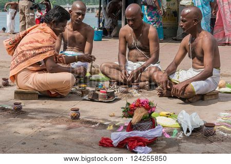 Trichy India - October 15 2013: Sitting in a mandala three brothers mourn their mother under the guidance of guru at Amma Mandapam.
