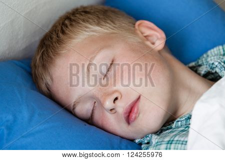 Close up of cute little blond boy under white blanket in blue bed asleep with closed eyes in flannel pajamas