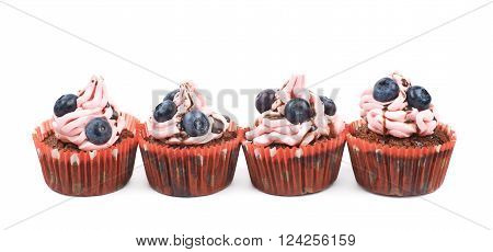 Chocolate muffin coated with the pink cream frosting and fresh bilberries, composition isolated over the white background