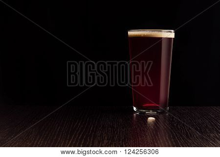The beer red ale. The dark background.