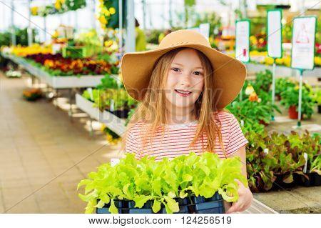 Kid girl buying vegetable seedlings in garden center