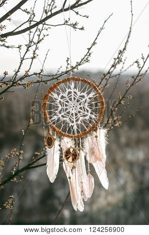 Handmade pink native american dream catcher on background of rocks and lake. Tribal elements feathers lace crochet snowflake doily