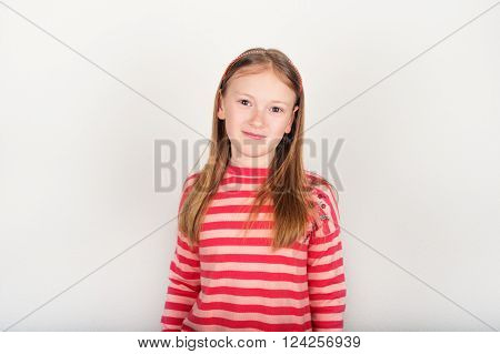 Studio portrait of adorable little girl of 8-9 years old, wearing coral color stripes pullover, standing against white background