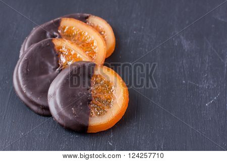 slices of orange coated chocolate on a black wooden background