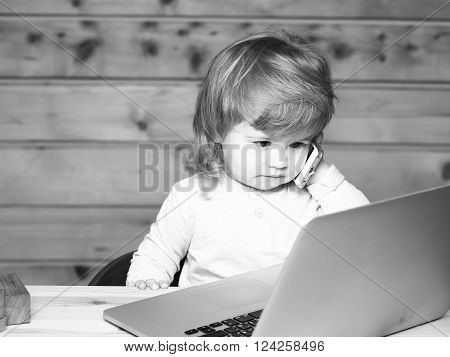 Cute funny little baby boy with long blonde curly hair speaking by mobile phone near computer indoor on wooden background horizontal picture