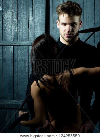 Young sensual couple of stylish man in shirt and pretty sexy topless woman with back embracing lover indoor on wooden background vertical picture
