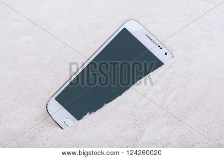 Mobile phone buried in the grey sand