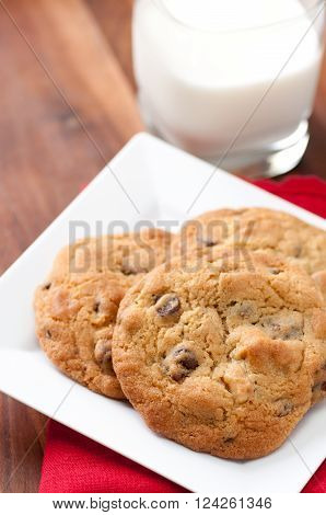 oven fresh home made chocolate chip and walnut cookies with a glass of milk