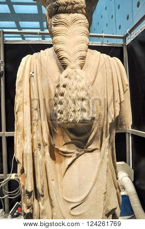 ATHENS GREECE - JANUARY 28 2011: Media press presentation of restoration and conservation work on the Caryatids at the New Acropolis Museum. Conservator using laser to remove surface contamination. Partially completed rear view.