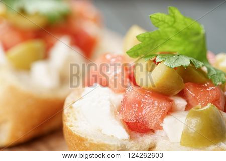 crostini with tomato, mozzarella and olives on wooden table