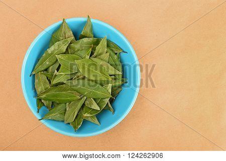 Ceramic Bowl Of Bay Leaves On Kraft Paper