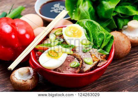 Duck noodles with egg and duck meat in bowl.