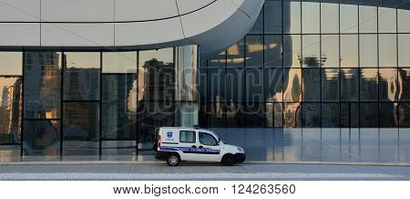 BAKU, AZERBAIJAN - MARCH 22 2014  Police car in front of the Heydar Aliyev Centre. An Azerbaijani policeman sits in his car in front of an iconic modern building designed by Zaha Hadid, in the centre of Baku