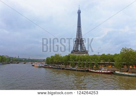 Eiffel Tower and Boats on Seine River in Paris in France in the evening. Eiffel Tower is an iron lattice tower of Paris. It is a global and cultural icon for France