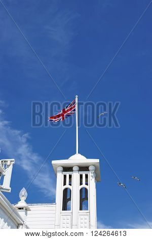 Tower with a US flag in Brighton Pier in East Sussex in the UK. It is also called Brighton Marine Palace and Pier or Palace Pier. It is under the protection of the UNESCO.