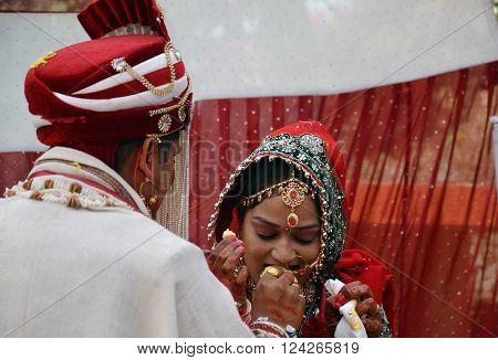 Shimla - Nov 28: Bride being fed ladoo(sweet) by groom during varmala ceremony on wedding day Shimla Nov 28 2013 in Himachal Pradesh, India, Asia.