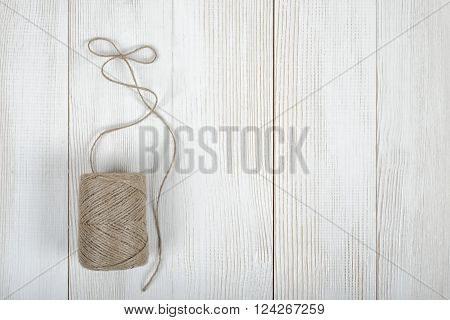 Twine on wooden DIY workbench with open space right side. Top view of the composition.