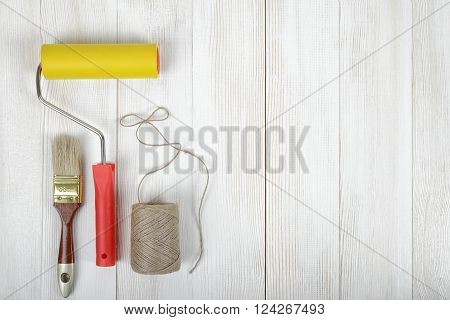Top view of construction instruments and tools on wooden DIY workbench with open space right side. Set of twine, brush and roller.