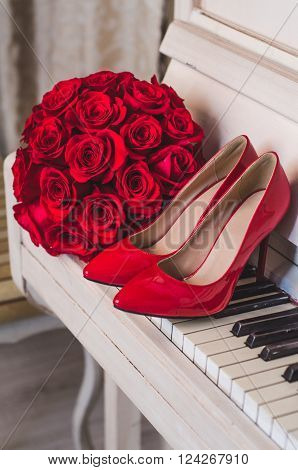 wedding details: bouquet of red roses flowers and elegant red bride's shoes stand on classic white piano in cafe