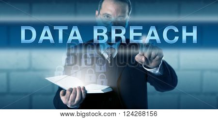 IT security practitioner pressing DATA BREACH onscreen. With concerned but focused look across his glasses the corporate professional is facing the challenge with lock icons emanating from a book.
