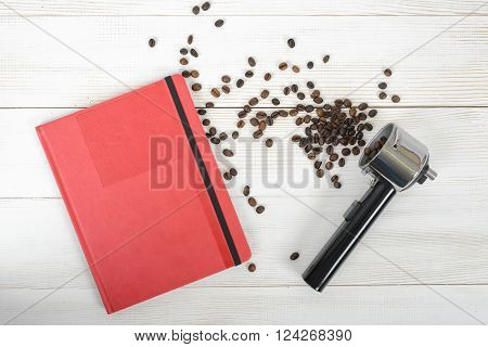 Coffee stuff with a portafilter of a home espresso machine, red folder and scattered coffee beans on wooden surface in top view