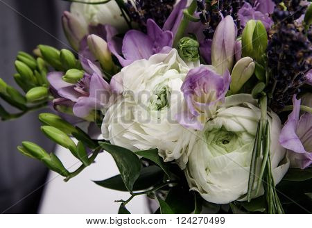 Beautiful spring bouquet of wedding flowers white, violet, green buttercup ranunculus, fresia. Background soft macro. Rustic style, still life. Holiday wedding floristic, bouquet of bride. Marriage.