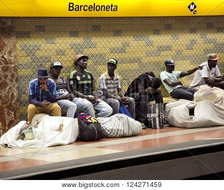 SPAIN, BARCELONA, JUNE, 28, 2015 - Street Vendors with large bales are waiting for a train in the subway in Barcelona, Spain. Street Vendors sell their merchandise, much of which is counterfeit.