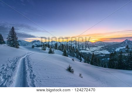 colorful sunset view from ski track on snowy filed at winter mountain