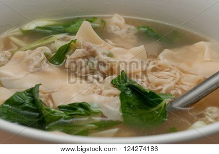 pork wontons in a clear broth with bok choy and ramen noodles