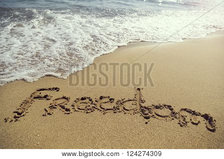 Word freedom handwritten in golden sand on the beach next to the waterline