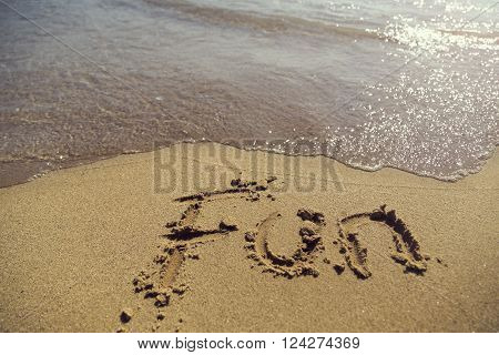 Word fun handwritten in sand on the beach next to the waterline