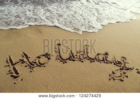 Word holiday handwritten in golden sand on the beach next to the waterline