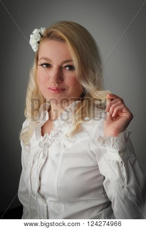 Blond woman in white looking innocently mischievous