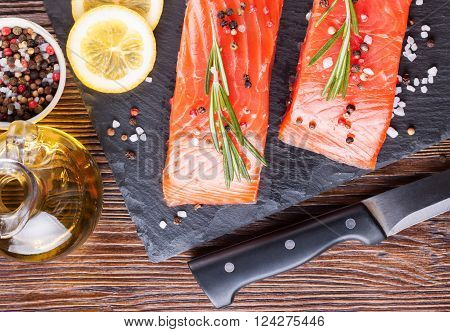 Raw salmon fillet and ingredients for cooking on a slade board and knife on  brown wooden background.