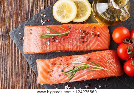 Raw salmon fillet and ingredients for cooking on a slade board and  brown wooden background. Top view