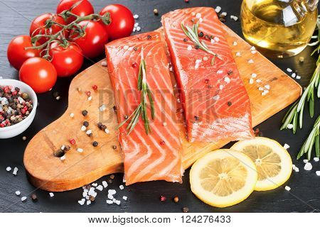 Raw salmon fillet and ingredients for cooking on a cutting board and  dark  slate background.