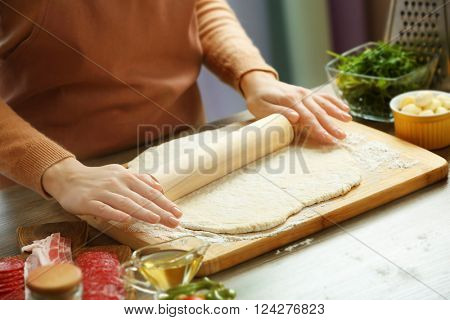 Woman rolling out a pizza dough on a wooden board, close up