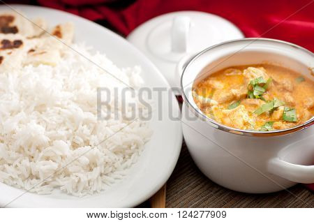 home made butter chicken and fresh naan bread on the side stock photo