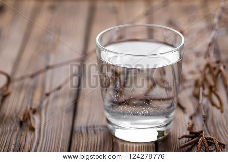 birch sap in a glass on a wooden table