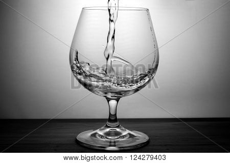 splash water in glass of cognac black and white