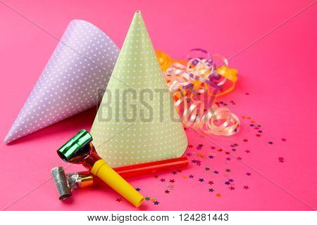Two dotted Birthday hats with serpentine streamer and noise makers on pink background