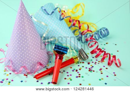 Dotted Birthday hats with serpentine streamer and noise makers on light blue background