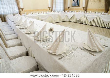 Beautifully organized event, glasses at served festive white tables ready.  Event in restaurant. Banquet, wedding decor, celebration. Catering and event. Wedding tables. Large restaurant hall.
