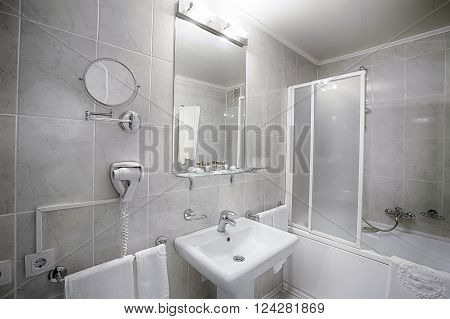 Interior design of a hotel bathroom. Hotel restroom interior design. Washbasins, sink, toilet, shower cabin and mirror. Clean public bathroom in hotel. Contemporary interior design. Modern bathroom.