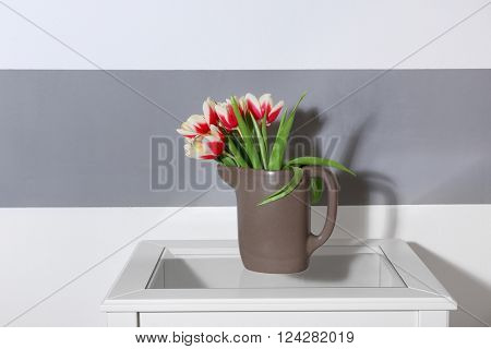 Bouquet of variegated tulips in jug on white table near striped wall
