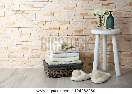 Towels, bath accessories and flowers on brick wall background