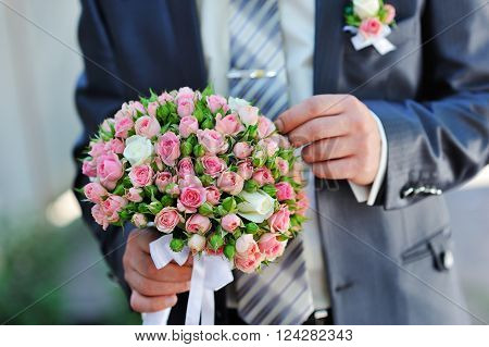 groom is holding a wedding bouquet in summer park